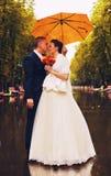 Paare unter Regenschirm auf nasser Gasse im Park Stockbild