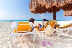 Paare unter Sonnenschirm in karibischem Meer Stockfotografie