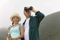 Paare unter Verwendung der Ferngläser in der Landschaft Stockfotos