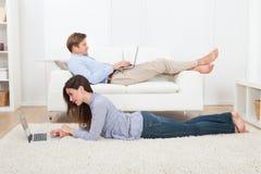 Paare unter Verwendung der Laptops im Wohnzimmer Stockfotos