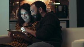 Paare unter Verwendung der Tablette auf Sofa nachts im Raum stock video footage