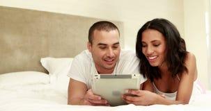 Paare unter Verwendung der Tablette zusammen im Bett stock footage