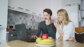 Paare unter Verwendung des Computers an der Küchenarbeitsplatte stock footage
