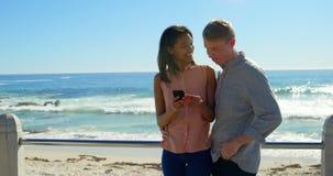 Paare unter Verwendung des Handys nahe Strand 4k stock footage