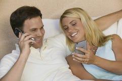 Paare unter Verwendung des Handys und PDAs Stockfoto