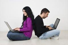 Paare unter Verwendung des Laptops Stockfotos