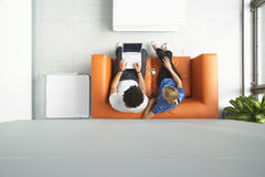 Paare unter Verwendung des Laptops auf orange Sofa At Office Stockbilder