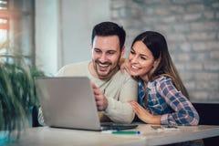 Paare unter Verwendung des Laptops auf Schreibtisch zu Hause stockbilder