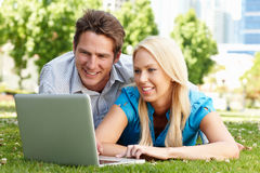 Paare unter Verwendung des Laptops im Stadtpark Lizenzfreies Stockbild