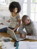 Paare unter Verwendung des Laptops mit Rechnungen Stockfotos