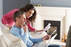 Paare unter Verwendung des Laptops und des Behandelns der Haushalts-Rechnungen Lizenzfreie Stockfotos