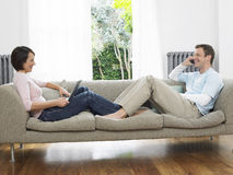 Paare unter Verwendung des Laptops und des Mobiltelefons auf Couch Stockfoto
