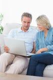 Paare unter Verwendung des Laptops zusammen auf der Couch stockfotografie