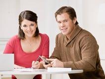 Paare unter Verwendung des Rechners, zum der Monatswechsel einzulösen Lizenzfreies Stockbild