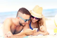 Paare unter Verwendung des Smartphone am Strand Lizenzfreies Stockfoto
