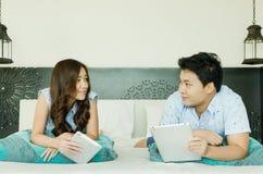 Paare unter Verwendung des Tablets auf dem Bett Stockbild