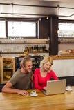 Paare unter Verwendung eines Laptops Lizenzfreie Stockbilder