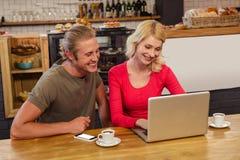 Paare unter Verwendung eines Laptops Stockbild