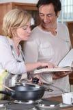 Paare unter Verwendung eines Rezeptbuches Lizenzfreie Stockfotos