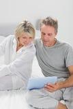 Paare unter Verwendung ihres Tabletten-PC stockfoto