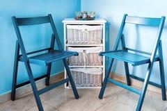 Paare von blauen Holzstühlen und von kleiner weißer Kommode nahe der Wand Stockbilder