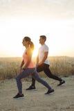 Paare von den Athleten, die Beine ausdehnen stockfotos