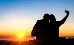Paare von den besten Freunden, die ein selfie bei Sonnenuntergang nehmen Stockbilder