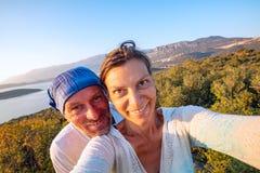 Paare von den frohen Reisenden, die selfie in den Bergen nehmen stockbilder