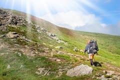 Paare von den jungen glücklichen Reisenden, die mit Rucksäcken auf schönen Rocky Trail am warmen sonnigen Tag wandern Familien-Re lizenzfreies stockbild