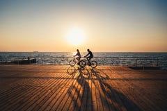 Paare von den jungen Hippies, die zusammen am Strand am Sonnenaufganghimmel zur hölzernen PlattformSommerzeit radfahren lizenzfreie stockfotos
