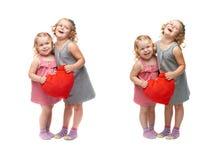 Paare von den jungen kleinen Mädchen, die über lokalisiertem weißem Hintergrund stehen Stockfotos