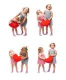 Paare von den jungen kleinen Mädchen, die über lokalisiertem weißem Hintergrund stehen Lizenzfreies Stockbild