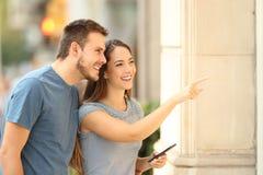 Paare von den Käufern, die ein Schaufenster auf der Straße aufpassen lizenzfreies stockbild