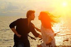 Paare von den Liebhabern, die auf den Fahrrädern auf der Küste bei Sonnenuntergang sitzen lizenzfreie stockbilder