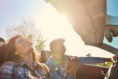 Paare von den Liebhabern, die auf ein konvertierbares Motor- Jungvermählten fahren, passen auf einem romantischen Datum zusammen Lizenzfreie Stockfotografie