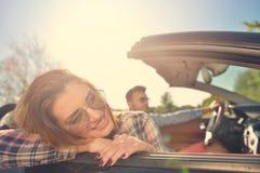 Paare von den Liebhabern, die auf ein konvertierbares Motor- Jungvermählten fahren, passen auf einem romantischen Datum zusammen Lizenzfreie Stockbilder