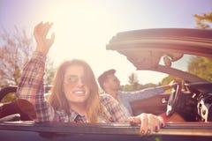 Paare von den Liebhabern, die auf ein konvertierbares Motor- Jungvermählten fahren, passen auf einem romantischen Datum zusammen Stockfoto