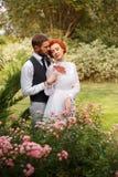 Paare von den Liebhabern, die in einem bunten Garten stehen Stockbilder