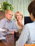 Paare von den Pensionären, die mit Angestelltem sprechen Stockfotografie