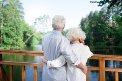 Paare von den Pensionären, die schönen See betrachtend sich umarmen stockfotos