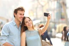 Paare von den Touristen, die ein selfie in einer Stadtstraße fotografieren stockfotografie