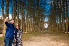 Paare von den Touristen, die ein selfie am Garten des Versailles-Palastes an einem einfrierenden Wintertag kurz vor Frühling nehm lizenzfreie stockfotos