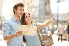 Paare von den Touristen, die eine Stadt konsultieren, führen das Suchen von Standorten lizenzfreies stockfoto