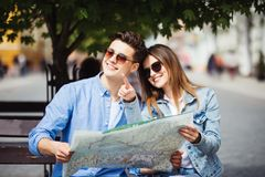 Paare von den Touristen, die den Standort sitzt auf Bank während einer Sommerreise auf Stadtstraße suchen stockbild