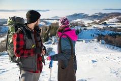 Paare von den Wanderern, die auf dem Berg stehen, wählen aus lizenzfreie stockbilder