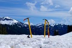 Paare von Eisäxten im Schnee gegen Berge Stockfotos