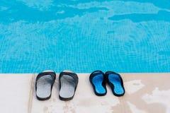 Paare von Flipflops nähern sich Pool stockfotos