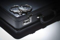 Paare von Handschellen und von Aktenkoffer unter Scheinwerferlicht Lizenzfreie Stockfotos