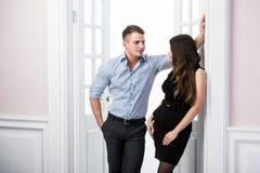 Paare von jungen stilvollen Leuten im Eingangsausgangsinnendachbodenbüro, das miteinander schaut Stockbilder
