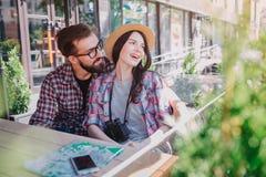 Paare von jungen Touristen sind in der Liebe Sie sitzen zusammen Sie schaut, um mit Seiten zu versehen Junger bärtiger Mann sie u stockbilder